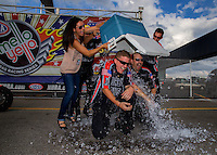 Sept. 1, 2014; Clermont, IN, USA; Anne Marie Kraweic (left) and Andrew Hines dump ice water on crew members Mike Mullaney and Scott Sceurman after winning the NHRA US Nationals at Lucas Oil Raceway. Mandatory Credit: Mark J. Rebilas-USA TODAY Sports