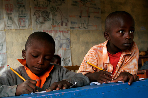 Denis Mutrtuia(Left) and Samwel Kithinji keep their eyes on their exams and their teacher at the Early Childhood Development school at Pepo La Tumaini Jangwani, a community based HIV/AIDS program in Isiolo, Kenya., on Tuesday, July  29, 2008.  (Photo by Bryce Yukio Adolphson, © 2008)