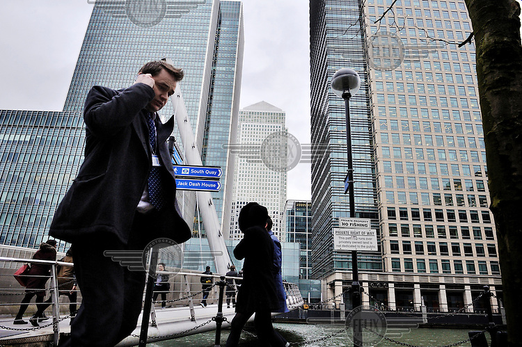A man, walking beneath the skyscrapers of Canary Wharf, London, uses his mobile phone. Behind him people are crossing the City Canal via the South Quay Footbridge.
