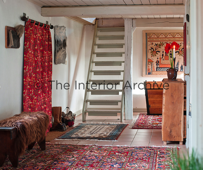 Oriental rugs, textile prints and a wall hanging decorated with a Dala motif make this staircase hall warm and cosy