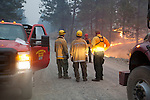 Fire-fighters confer in the middle of Sinlahekin Road in Okanogan County, WA.  Vehicle at left is owned by contract fire-fighting company.  Vehicle at right is from New Jersey.  Burn-out proceeding in woods.