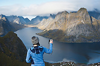 Female hiker takes photo of mountain landscape, Reine, Lofoten Islands, Norway