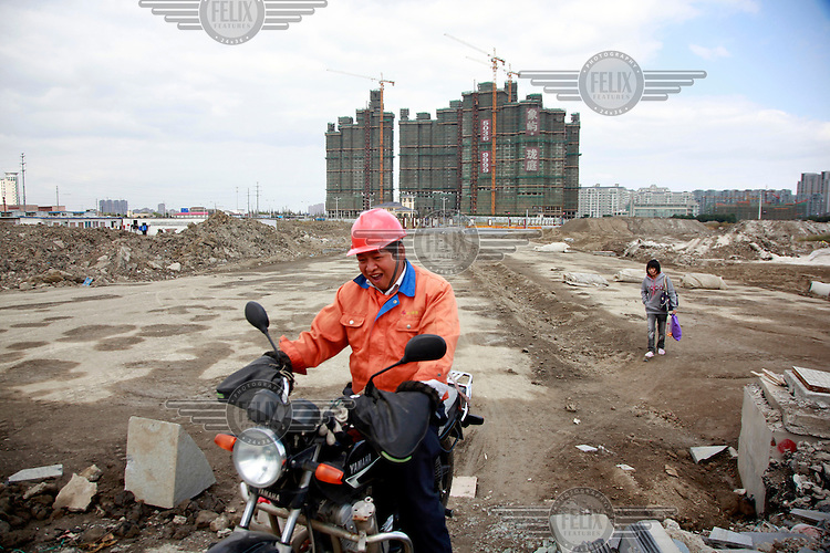 A laughing man rides a motorbike across a building site for a new housing development.