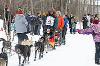 Sean Underwood and team run past spectators on the bike/ski trail near University Lake with an Iditarider in the basket and a handler during the Anchorage, Alaska ceremonial start on Saturday, March 7 during the 2020 Iditarod race. Photo © 2020 by Ed Bennett/Bennett Images LLC