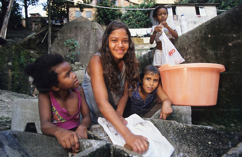 WASHING CLOTHES OUTSIDE. Rocinha Favela, Rio de Janeiro, Brazil, South America. Teenage girl and children washing clothes. Although Rocinha is technically classified as a neighborhood, many still refer to it as a favela. It developed from a shanty town into an urbanized slum. Today, almost all the houses in Rocinha are made from concrete and brick. Some buildings are three and four stories tall and almost all houses have basic sanitation, plumbing, and electricity. Compared to simple shanty towns or slums, Rocinha has a better developed infrastructure and hundreds of businesses. There is also lots of deliquency, crime and drugs in the favelas.