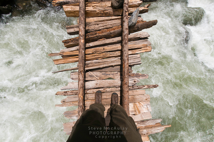 Point of view shot of trekker crossing the swollen Kanka River on a rickety wodden bridge, Naranag, Gangabal Lake region, Kashmir Himalayas, India