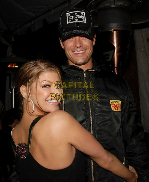 FERGIE & JOSH DUHAMEL .Fergie's Birthday Party at Citizen Smith Nightclub in Hollywood , California, USA..March 28th, 2006.Ref: DVS.Stacey Ferguson Black Eyed Peas half length baseball cap hat couple hug embrace jacket.www.capitalpictures.com.sales@capitalpictures.com.Supplied By Capital PIctures.
