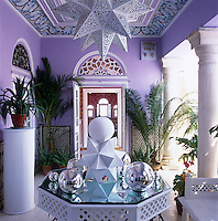 Custom-made polyhedra and mirrored glass baubles are a feature of the colourful veranda with its potted palms and hand-made ceiling lantern