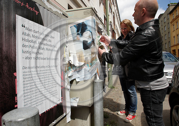 """BERLIN - GERMANY 25 MAY 2010 -- The danish satire artists Jan Egesborg and Pia Bertelsen from the artist group SURREND in Auguststrasse while they puts up their newest Israel critical poster -- PHOTO: CHRISTIAN T. JOERGENSEN / EUP & IMAGES....This image is delivered according to terms set out in """"Terms - Prices & Terms"""". (Please see www.eup-images.com for more details)"""