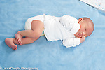 3 day old newborn baby boy full length lying on side sleepy, waking up