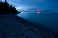 The far side of the Majuro lagoon is marked by the lights of Majuro, as seen before dawn from Eneko Island, Marshall Islands.