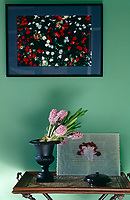 A tray table in the living room carries a vase of hyacinths and an artwork by Jose-Maria Sicilia