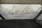 Bellmore, New York, USA. May 29, 2015. Closeup of large signature of Carroll Shelby, iconic American automotive designer and racing driver, is shown inside open trunk of an original Black 1965 Shelby Cobra 427 roadster race car at the Friday Night Car Show, held at the Bellmore Long Island Railroad Station Parking Lot. Hundreds of classic, antique, and custom cars are generally on view at the free weekly show, sponsored by the Chamber of Commerce of the Bellmores, from May to early October.