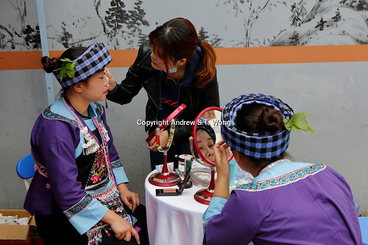 Young women of the ethnic Bouyei Tribe puts on makeup at Wangmo County in China's southwestern Guizhou Province, April 2019.