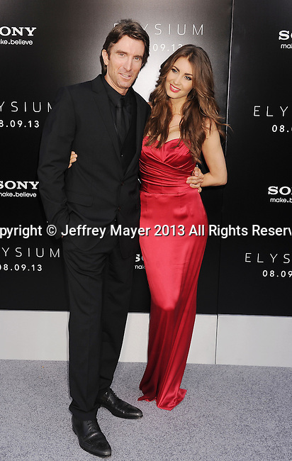 WESTWOOD, CA- AUGUST 07: Actor Sharlto Copley and model Tanit Phoenix arrive at the Los Angeles premiere of 'Elysium' at Regency Village Theatre on August 7, 2013 in Westwood, California.