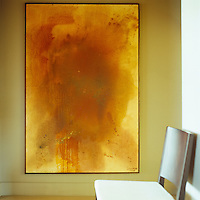 In the entrance hall a large abstract painting signed Loukiana works as a burst of sunshine against the pale olive walls