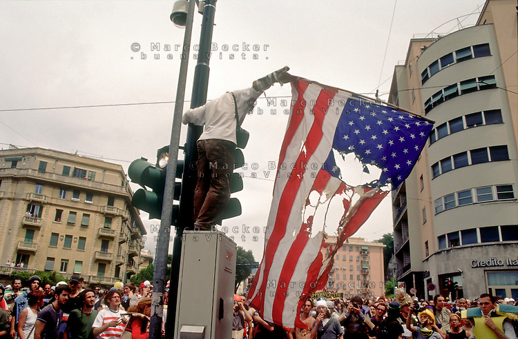 Genova luglio 2001, proteste contro il g8. Un manifestante tenta di bruciare una bandiera degli Stati Uniti d'America --- Genoa july 2001, protests against g8 summit. A demonstrator tries to burn a flag of the United States of America