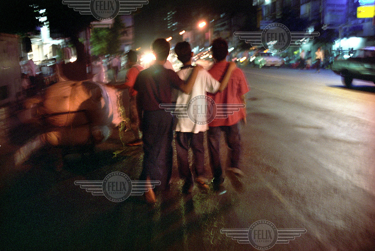 "Three young men walk down a street in the Chinatown area of Rangoon (Yangon) during the night. According to one of them ""we're just like any other men, just looking for fun. If the foreigner wants to pay us, let them, I say."". In recent years, Burma has experienced an increase in both homosexual and heterosexual sex tourism. .."
