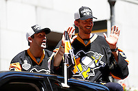 Bryan Rust #17 of the Pittsburgh Penguins and Matt Murray #30 of the Pittsburgh Penguins wave to the crowd during the Stanley Cup victory parade in downtown Pittsburgh, Pennsylvania on June 15, 2016. (Photo by Jared Wickerham / DKPS)