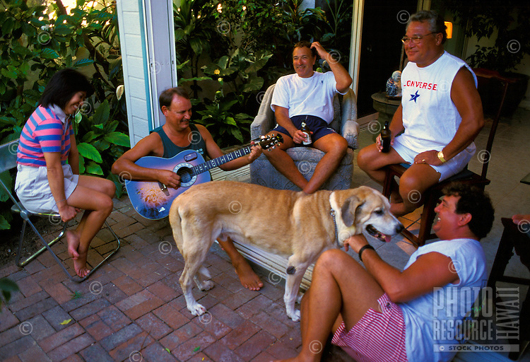 Local musician Jerry Santos plays guitar while relaxing with friends