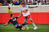 Shea Salinas (22) of the Vancouver Whitecaps goes for a tackle on Chris Albright (3) of the New York Red Bulls. The New York Red Bulls and the Vancouver Whitecaps played to a 1-1 tie during a Major League Soccer (MLS) match at Red Bull Arena in Harrison, NJ, on September 10, 2011.