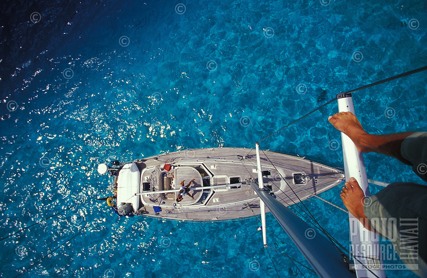 Mast head view of sailing yacht 'Heron' with crew on deck and swimming, at anchor in clear lagoon waters of Raiatea, Society Islands, French Polynesia