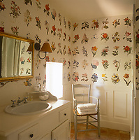 A pretty country bathroom with part panelled wall and floral patterned wallpaper above the panelling. A washbasin is set in a white cupboard unit.