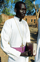 Sudan. South Sudan. Bahr El Ghazal. Mayen Abun. Catholic dinka priest getting ready to celebrate the sunday mass. He hold in his hands the holy bible and has around his neck the holy cross with Jesus.  © 1999 Didier Ruef