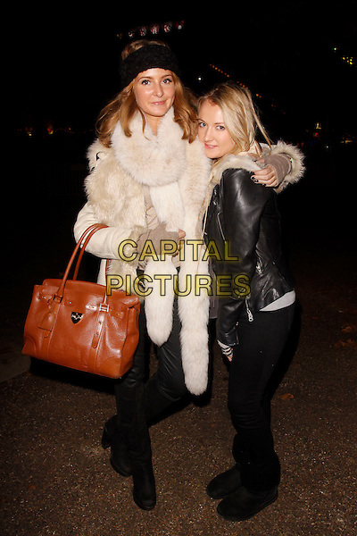 Millie Mackintosh & guest.The Winter Wonderland launch party, Hyde Park, London, England..November 17th, 2011.full length black fur suede jacket coat gloves brown bag purse jeans denim .CAP/AH.©Adam Houghton/Capital Pictures.