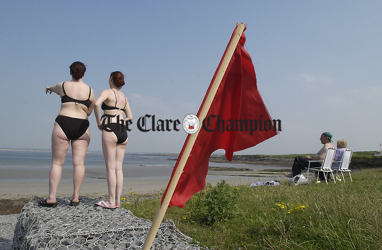 All togged out and nowhere to go.... potential swimmers can only admire the view as the lifeguard's red flag marks the sea at White Strand, Doonbeg as a no go area. Photograph by John Kelly.