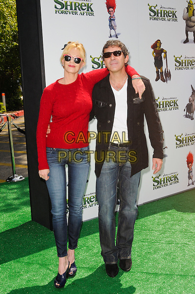 "MELANIE GRIFFITH & ANTONIO BANDERAS .at DreamWorks Animation's ""Shrek Forever After"" L.A. Film Premiere held at Gibson Amphitheatre at Universal CityWalk, Universal City, California, USA, May 16th, 2010. .arrivals full length red jumper cable knit sweater ray bans sunglasses wayfarers jeans black jacket white t-shirt arm around married couple husband wife jeans .CAP/ROT.©Lee Roth/Capital Pictures"