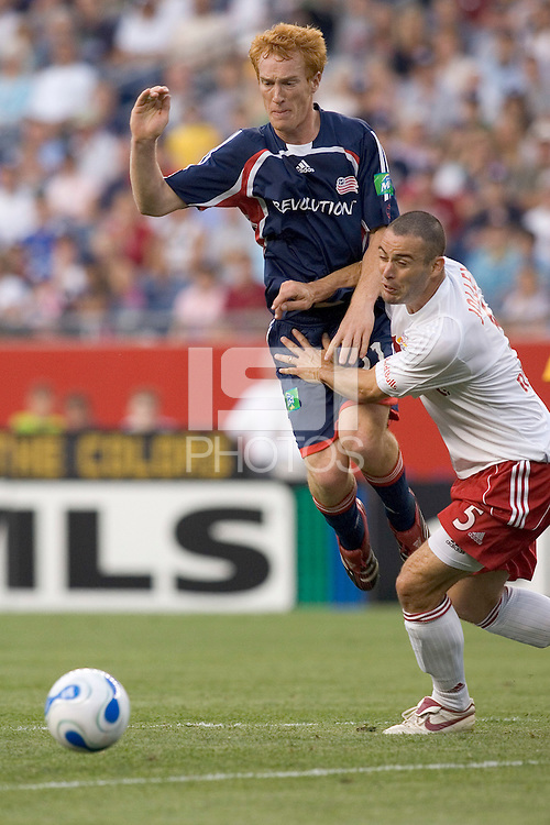 Steve Jolley (Red Bull NY, white) using both hands to slow down Jeff Larentowicz (Revolution, blue). The New England Revolution defeat Red Bull NY, 3-2, July 1at Gillette Stadium.