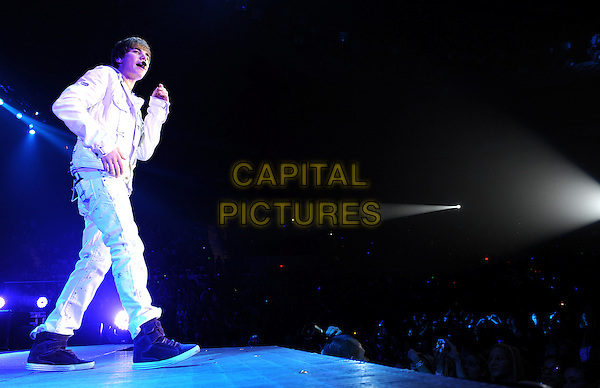 JUSTIN BIEBER .performs live at the Scope Arena,  Norfolk, Virginia, USA, .13th November 2010..music concert live on stage gig full length white top trousers purple trainers hi-tops jacket singing  hood hoodie  .CAP/ADM/MOO.© Moose/AdMedia/Capital Pictures.