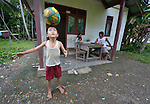 "Ferianus Laia, 9, practices his football skills in front of his house in Tugala, a village on the Indonesian island of Nias. His family sits behind him. The village was struck by both a 2004 tsunami and a 2005 earthquake, leaving houses destroyed and lives disrupted. The ACT Alliance helped villagers here to construct new homes and latrines, build a potable water system, open a clinic and schools and get their lives going once again. For the residents of Tugala, the post-disaster mantra of ""build back better"" became a reality with help from the ACT Alliance."