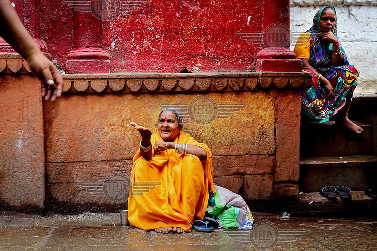 A female Sadhu (Sadhvi) begging for alms outside a temple.