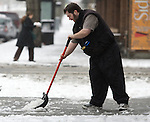 Haakon Steindol clears a sidewalk of snow after a snowstorm hit the Seattle area early morning dumping at least 4 to six inches and will likely continue into the afternoon it a tough commute for drivers  in Seattle on January 18, 2012.  ©2012. Jim Bryant Photo. All Rights Reserved.