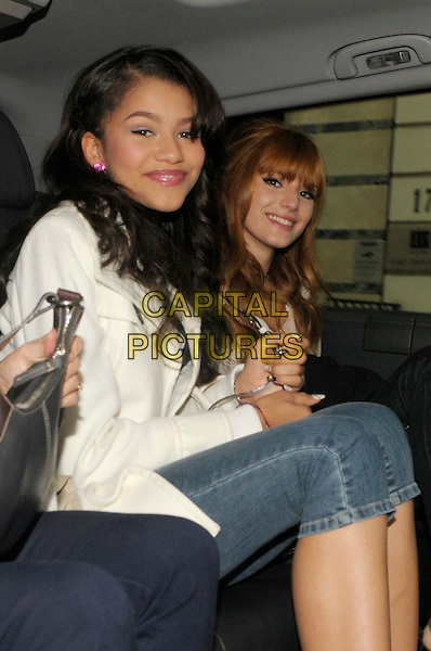 Zendaya Cole & Bella Thorne from the Disney show 'Frenemies' in central London, England..17th May 2012.half 3/4 length jeans denim beige top gold sitting side shorts jean mac white.CAP/IA.©Ian Allis/Capital Pictures.