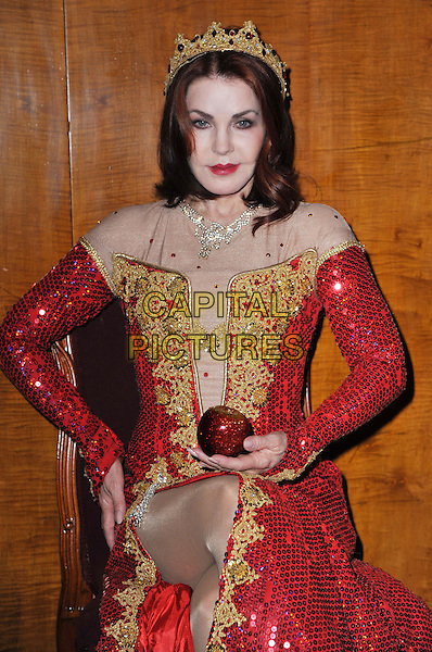 Priscilla Presley.Press launch to star in New Wimbledon Theatre's annual pantomime offering 'Snow White and the Seven Dwarfs' at The Savoy, Strand, London, England..September 26th, 2012.panto costume half length gold red dress crown sequins sequined apple  sitting slit split .CAP/BF.©Bob Fidgeon/Capital Pictures.