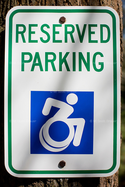 Parking spaces at Gordon College display the previous two-wheel version of the Accessible Icon. The icon, designed by the Accessible Icon Project, is a redesign of the International Symbol of Access (also known as the handicap symbol) that shows an active and engaged person with arms in motion.  Glenney's research focuses on the philosophy of perception and he maintains active interest in graffiti and street art.  The Accessible Icon has been adopted by cities and institutions around the world, including Gordon College, Nissan, New York City, Malden, MA, and others.