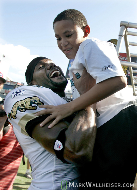 Jacksonville Jaguars wide receiver Jimmy Smith (L) celebrates the Jaguars' 27-14 win over the Seahawks by pulling his son, Jimmy, 9, out of the stands in Jacksonville, Florida September 11, 2005.