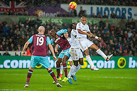 Andre Ayew of Swansea ( right ) jumps for the ball during the Barclays Premier League match between Swansea City and West Ham United played at the Liberty Stadium, Swansea  on December 20th 2015