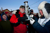 Iditarod development director Greg Bill hands the Widows Lamp to last place musher and red lantern award winner Celeste Davis to extinguish at the finish in Nome during the 2010 Iditarod