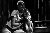 A Cuban woman poses for a picture with her amstaff dog during a sunny morning in Havana, Cuba, 9 February 2009.