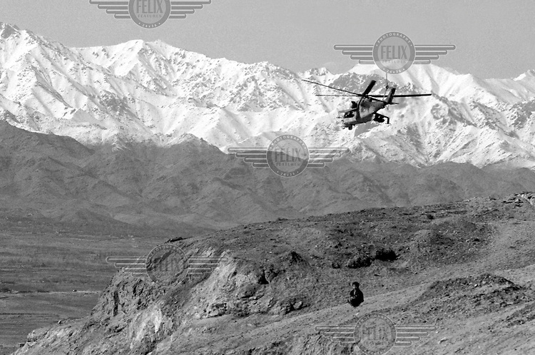 "A Soviet Mi-24 ""Hind"" helicopter escorts a fuel convoy on its way to the Afghan capital Kabul on Sunday, February 5, 1989. Under siege for several years, the regime in Kabul depends heavily on Soviet military support."