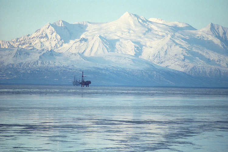 Oil and natural gas production platforms stand in Cook Inlet, offshore from Nikiski, Alaska, in front of Mount Spurr volcano in the Alaska Range.