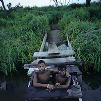 Brothers Joseph and Jasmon Jackson stay close to the bridge when they lower themselves into the muddy water of the drainage canal across the street from their house on Island Road on Isle Jean Charles, Louisana. In the past, most children swam and played in the waterways and bayous on the Island, but increasingly, parents worry about dangerous rubbish and contamination found there. The island is clinging to life after decades of severe erosion of coastal marshes that once provided a buffer against hurricanes and high tides. Only 70 or so residents remain, down from 300 at its peak.