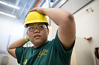 UAA College of Engineering build team member Mark Credito dons his hard hat before participating in a bridge-building demo at the send-off for the American Institute of Steel Construction (AISC) Steel Bridge Competition in the UAA Engineering and Industry Building Structures Lab.