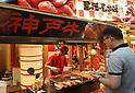 Foreign tourists stroll the Kuromon Ichiba market to enjoy fresh foods in Osaka