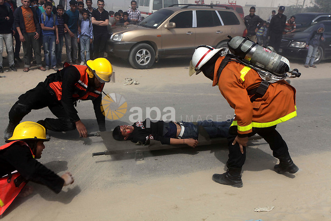 Palestinian Civil Defense members take part in a drill at a scene simulating a fire at a site struck by an Israeli air strike, in Beit Lahiya, in the northern Gaza Strip March 14, 2013. Photo by Ashraf Amra