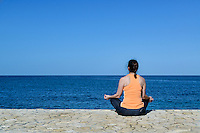 Woman practicing oceanfront yoga meditation.
